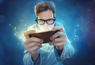 Guy with spectacles playing game on mobile