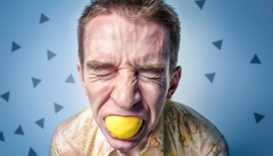 man Squeezing lemon in mouth